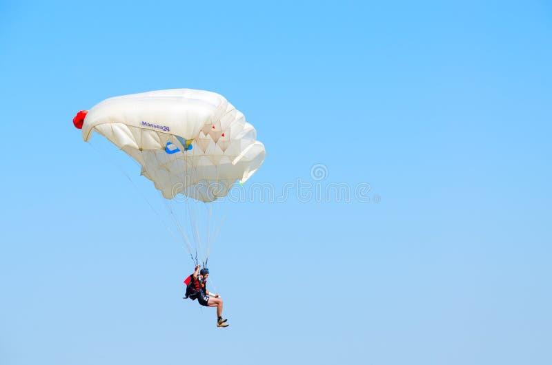 Homme - le parachutiste exécute le saut sur le fond du ciel bleu sans nuages photo stock