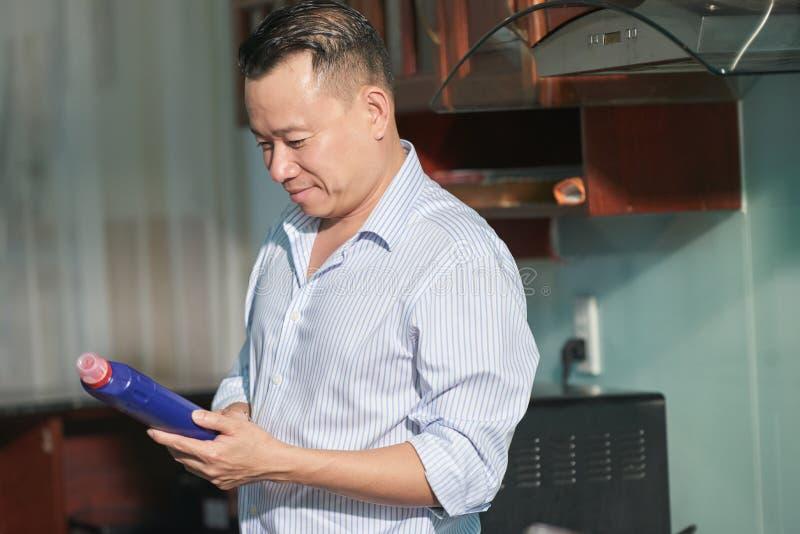 Homme lisant les instructions sur le décapant images stock