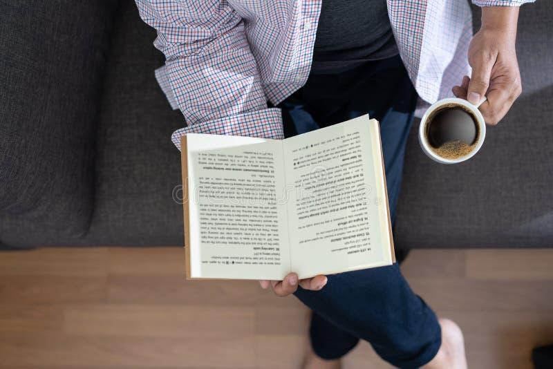 Homme lisant un livre et tenant la tasse de café Sit Read Knowledge images stock