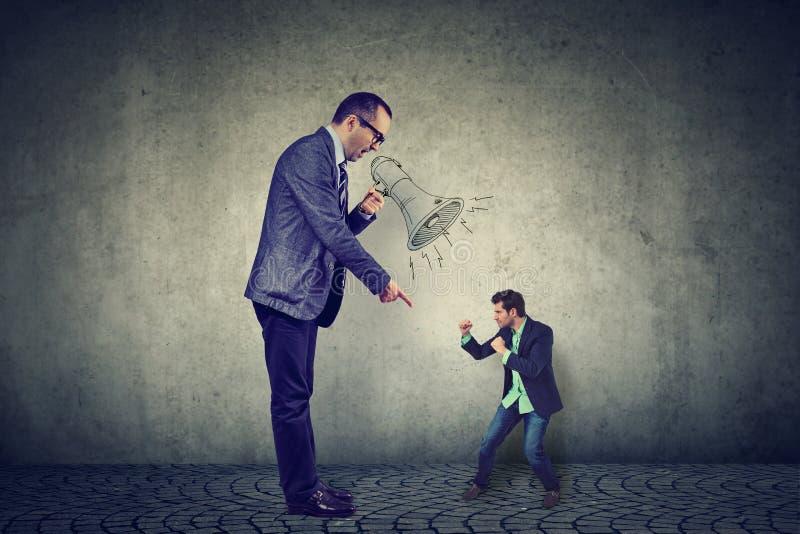 Homme luttant contre son grand patron fâché photos stock