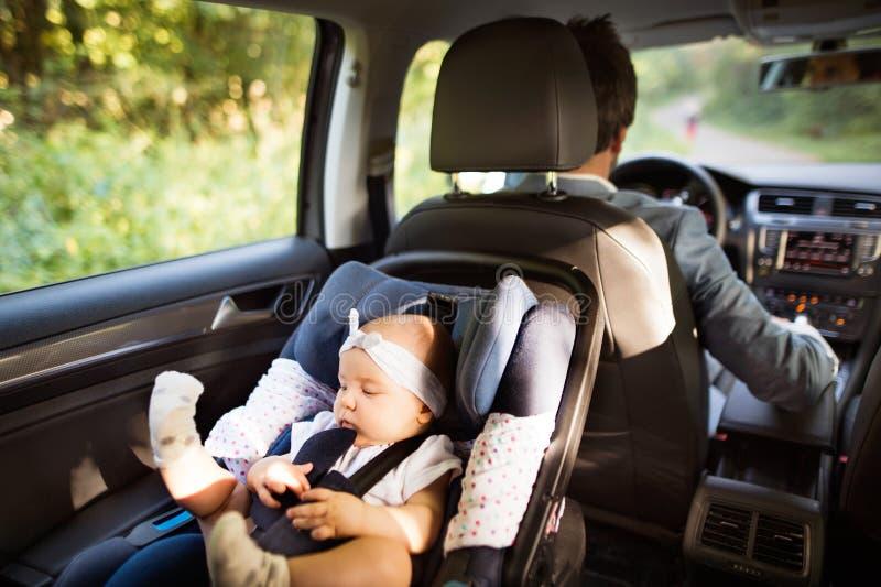 Homme méconnaissable conduisant avec un bébé photo libre de droits