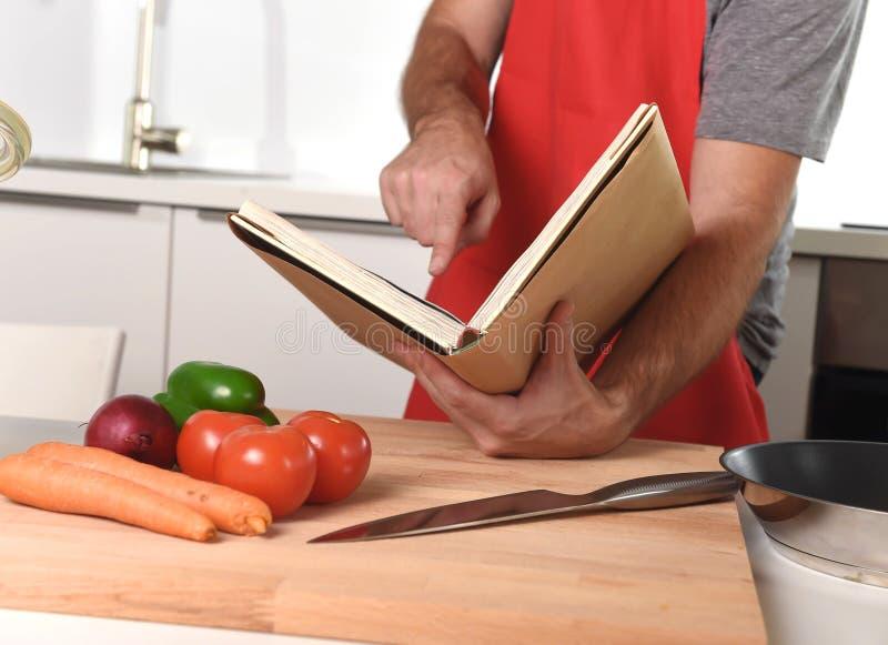 Homme méconnaissable dans le tablier à la cuisine après la cuisson saine de livre de recette images stock