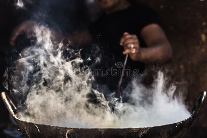 Homme méconnaissable faisant cuire dans la grande casserole ou wok fatiscent dans une petite stalle de nourriture de rue Fumée bl photos stock