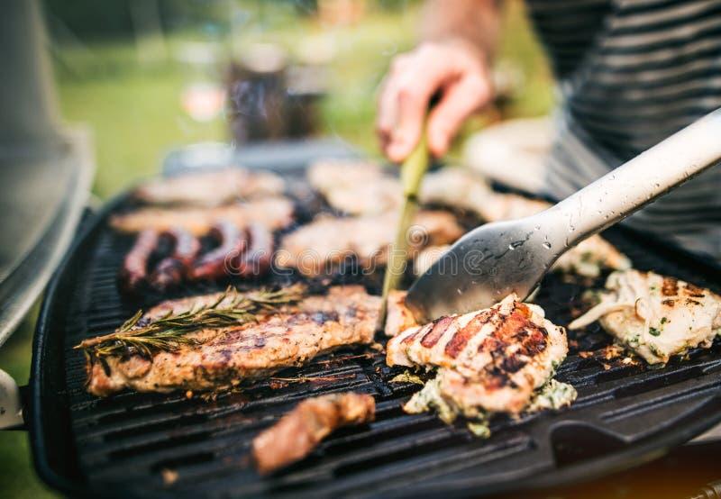 Homme méconnaissable faisant cuire des fruits de mer sur un gril de barbecue dans l'arrière-cour Fin vers le haut photo libre de droits