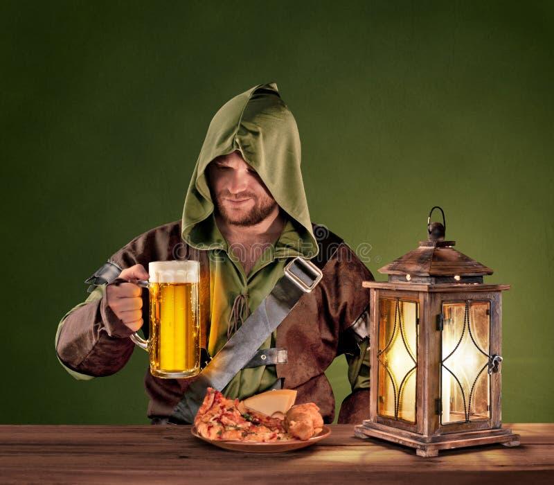 Homme médiéval dans une taverne avec de la bière sur le fond de vintage photos stock