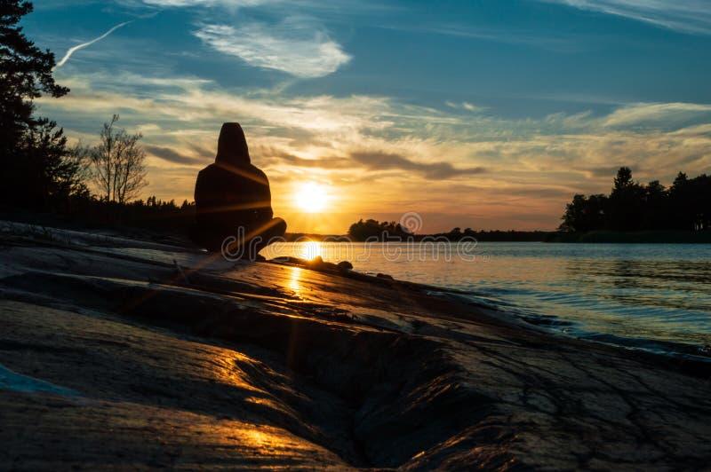Homme méditant, yoga au coucher du soleil photo stock