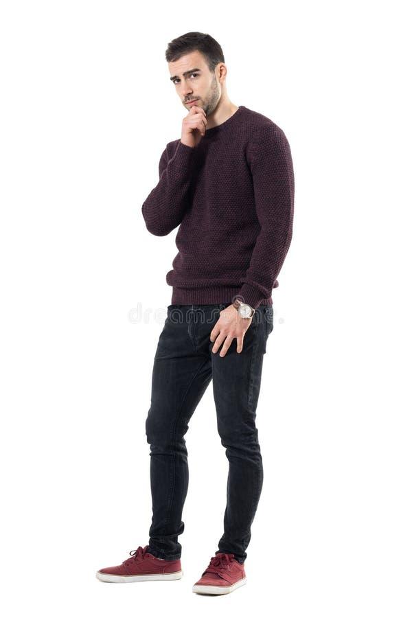 Homme méfiant sceptique avec des mains sur le menton regardant l'appareil-photo méfiant image stock