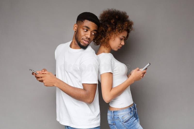 Homme méfiant tourné de nouveau à la femme, message de lecture au téléphone photographie stock