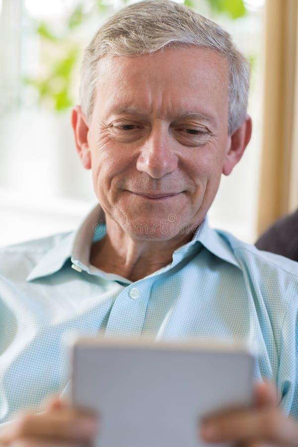 Homme mûr à l'aide du comprimé numérique à la maison images libres de droits