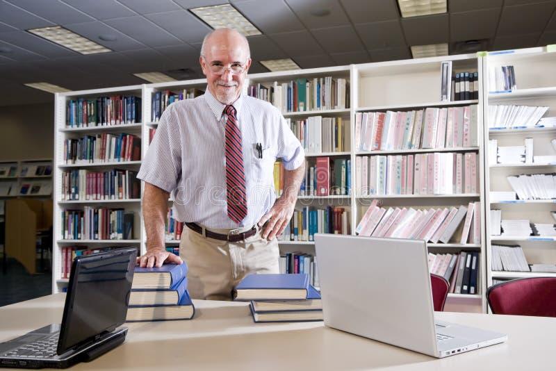 Homme mûr à la table de bibliothèque avec des manuels photos libres de droits