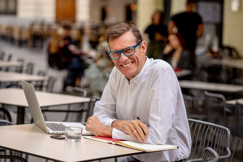 Homme mûr élégant attirant heureux travaillant sur l'ordinateur portable tout en ayant le café dans le café extérieur images libres de droits