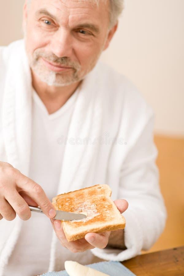 Homme mûr aîné ayant le pain grillé de déjeuner photo stock