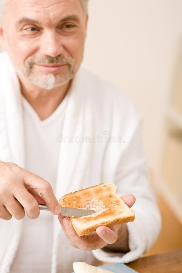 Homme mûr aîné ayant le pain grillé de déjeuner photographie stock
