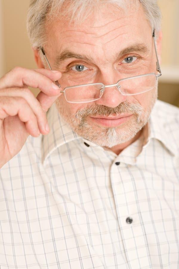 Homme mûr aîné pensif avec des glaces photo stock