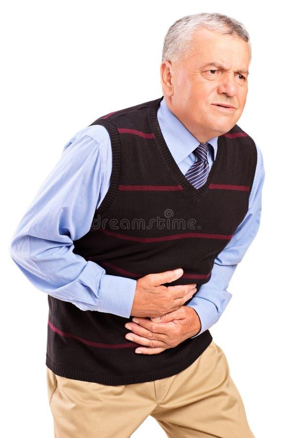 Homme mûr accablé avec une douleur dans l'estomac image stock