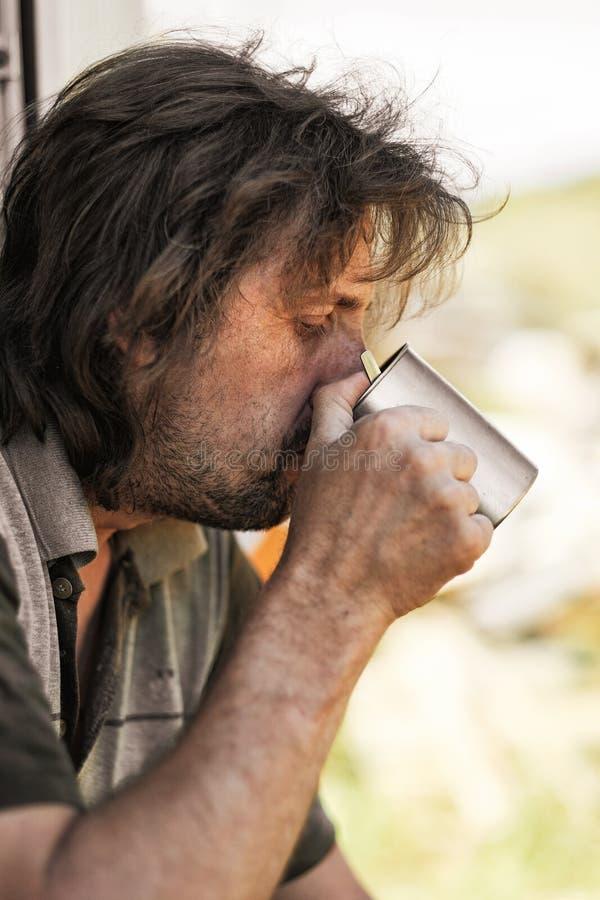 Homme mûr attirant buvant de la tasse de fer en dehors de la ville photo stock