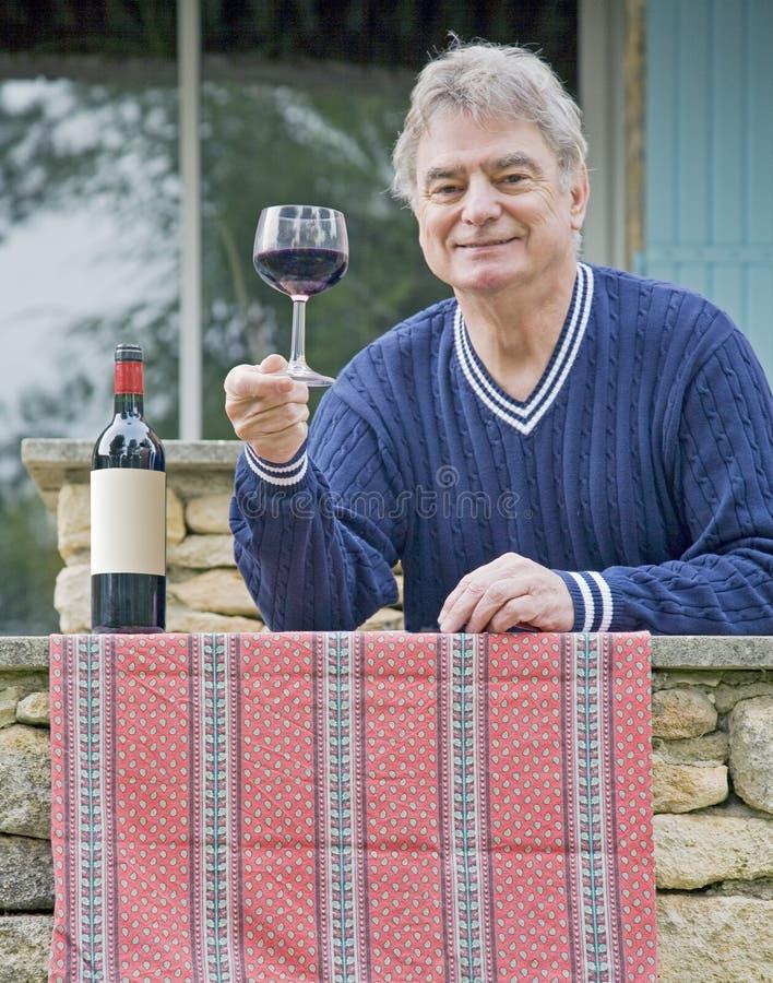 Homme mûr avec du vin photographie stock libre de droits