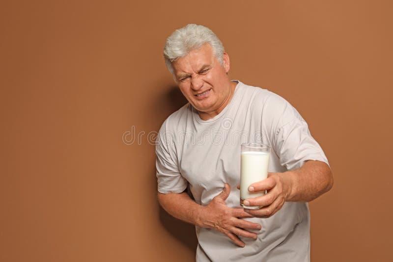 Homme mûr avec l'allergie de laiterie tenant le verre de lait images stock
