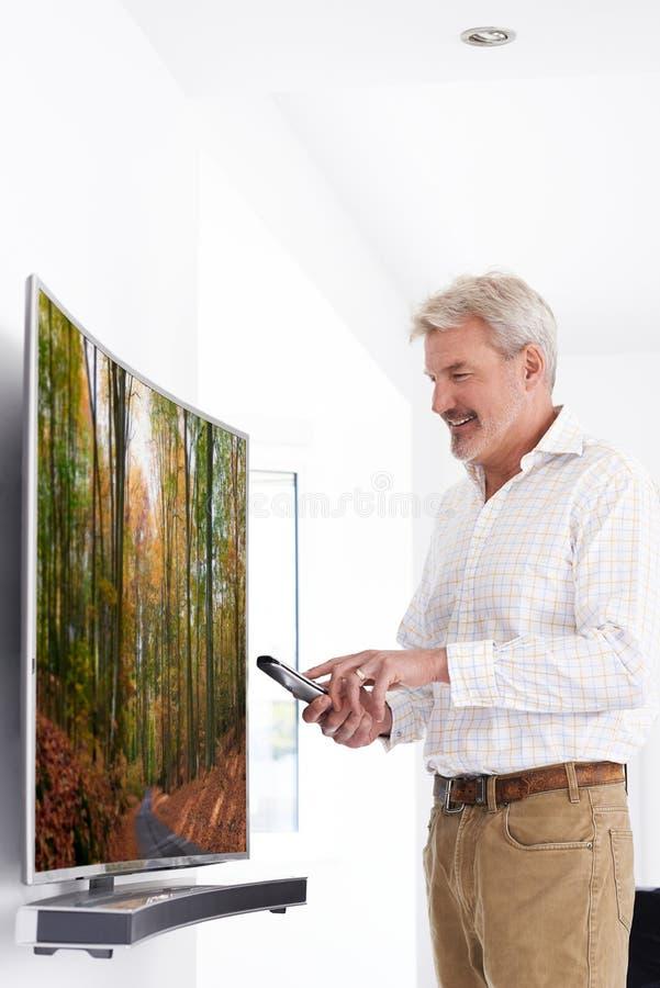 Homme mûr avec la nouvelle télévision incurvée d'écran à la maison photo stock