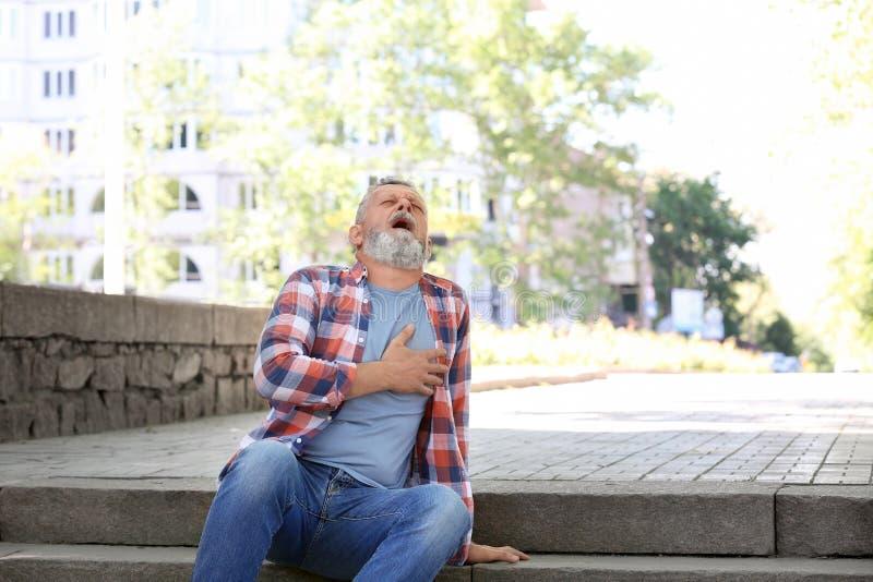 Homme mûr ayant la crise cardiaque sur des escaliers photographie stock libre de droits