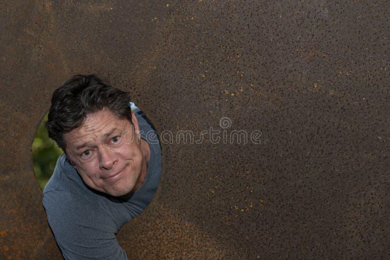 Homme mûr bel dans le trou de plat de fer, regardant l'appareil-photo, expressions du visage image libre de droits