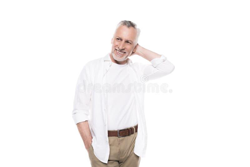 Homme mûr bel de sourire posant avec la main derrière la tête et regardant loin photos stock