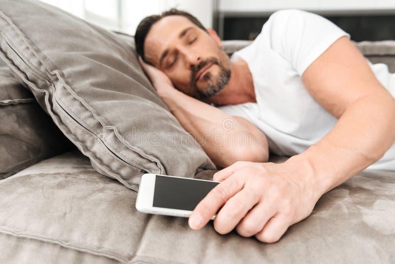 Homme mûr bel dormant sur un divan photo libre de droits
