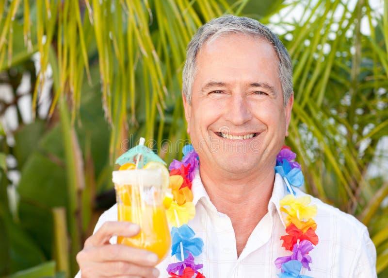 Homme mûr buvant un cocktail sous le soleil image libre de droits