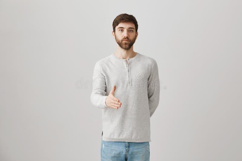 Homme mûr calme, tenant la main derrière tout en étirant des autres pour la poignée de main, se tenant avec sûr et sérieux photo libre de droits