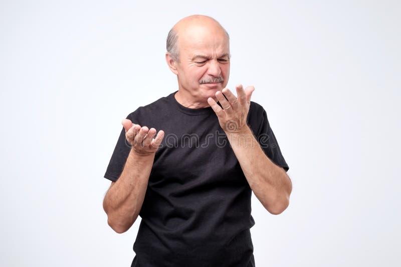 Homme mûr chauve dans le T-shirt noir sentant quelque chose désagréable et mauvaise image libre de droits