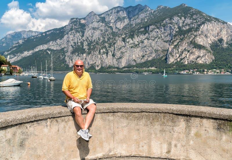 Homme mûr chauve de sourire s'asseyant sur le rivage du lac Como photo stock