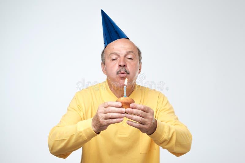 Homme mûr dans la bougie de soufflement de chapeau d'anniversaire sur son gâteau faisant un souhait photographie stock