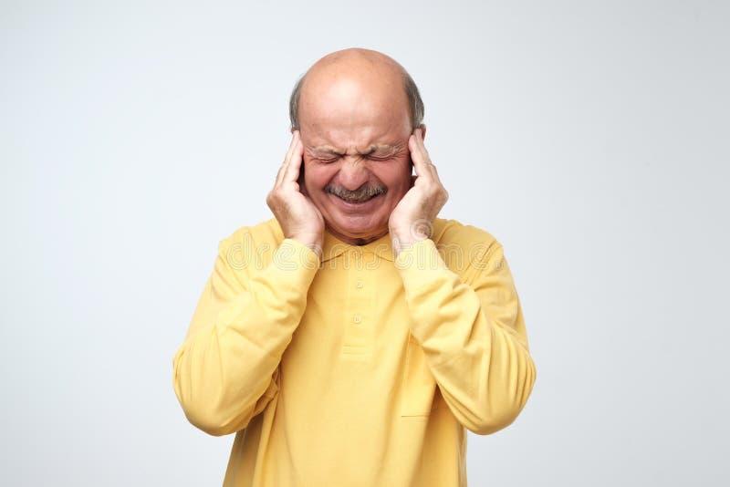 Homme mûr dans le T-shirt jaune souffrant de l'essai criard bruyant de musique et de douleur de brancher des oreilles sur le fond photos stock