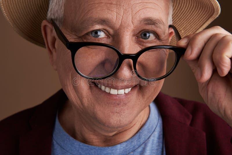 Homme mûr de sourire touchant les verres sur son visage photo stock