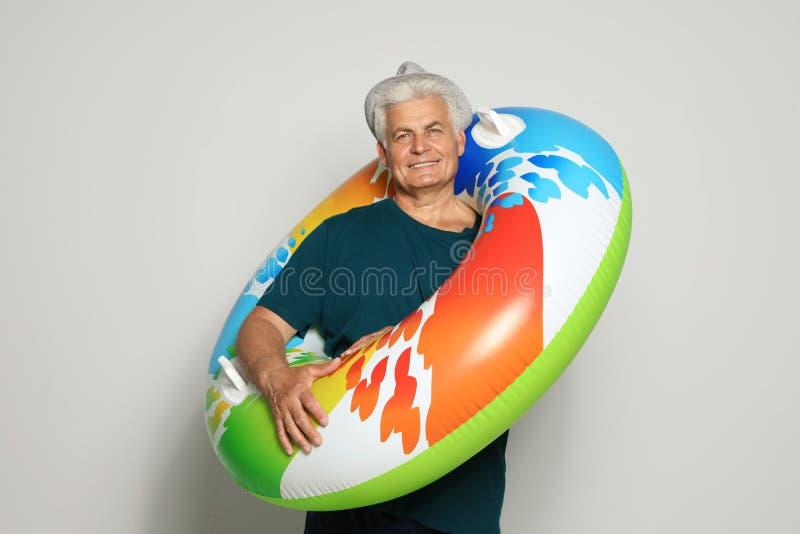 Homme mûr drôle avec l'anneau gonflable lumineux sur la lumière images stock