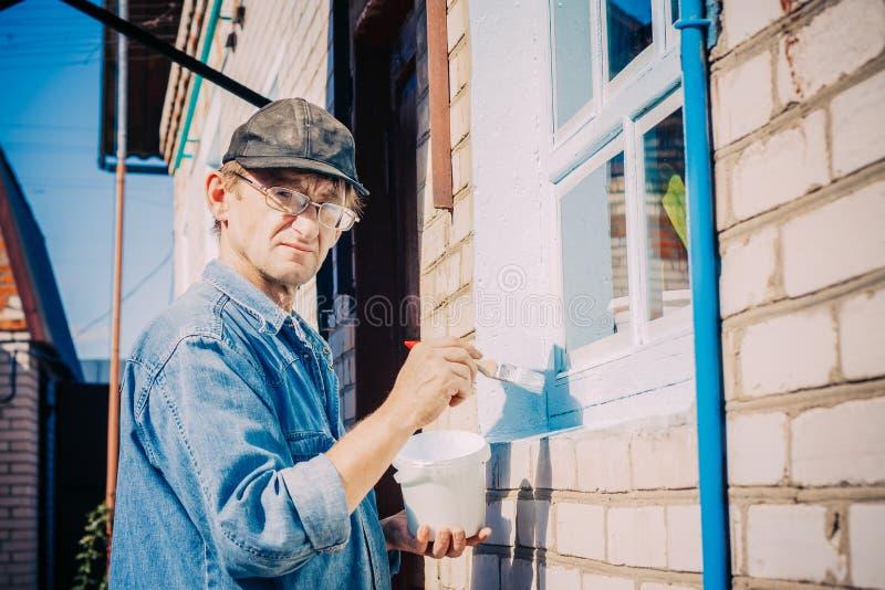 Homme mûr en verres, châssis de fenêtre de peinture en dehors de privé images stock