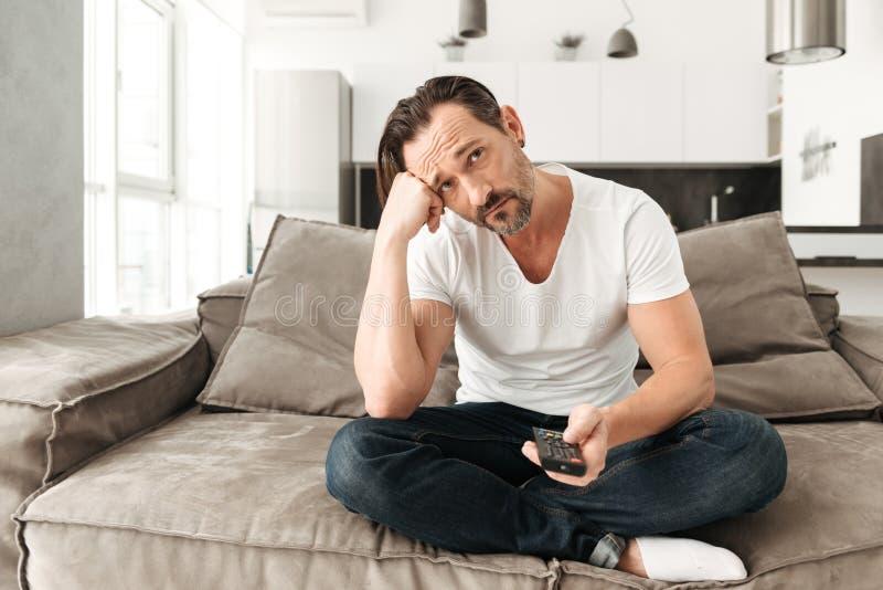 Homme mûr ennuyé s'asseyant sur un sofa images stock