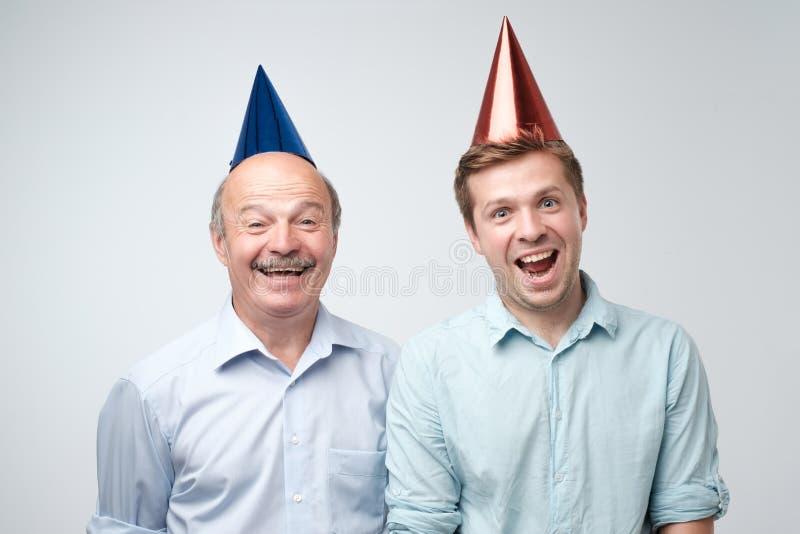 Homme mûr et son jeune fils célébrant le joyeux anniversaire utilisant les chapeaux drôles images stock
