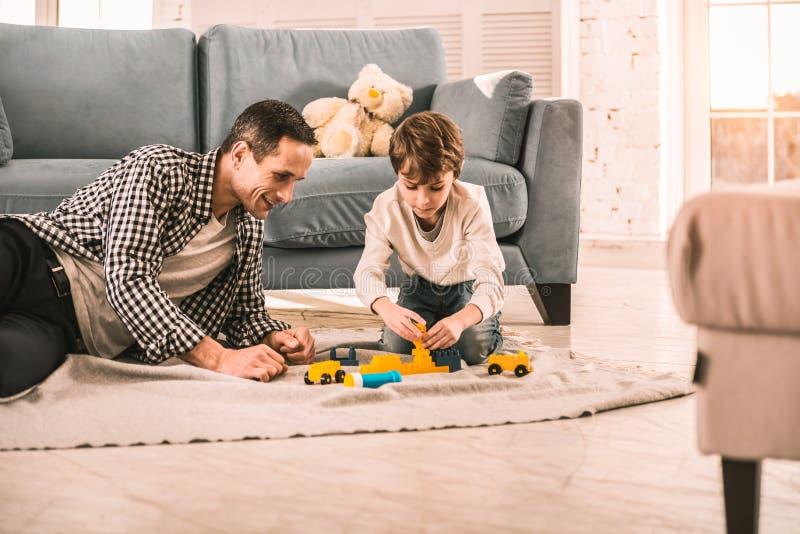 Homme mûr fasciné par la variété des jouets de son fils image libre de droits