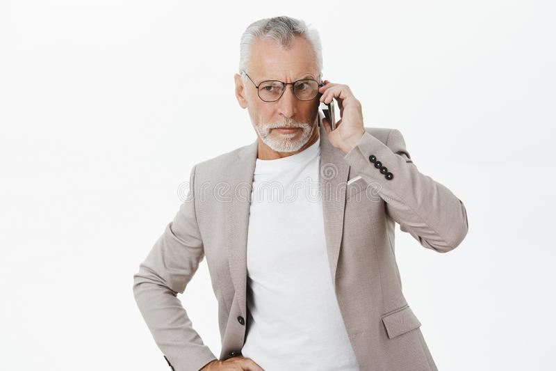 homme mûr focalisé autoritaire et déterminé à l'air sérieux avec les cheveux blancs et barbe dans les verres et le costume élégan image stock