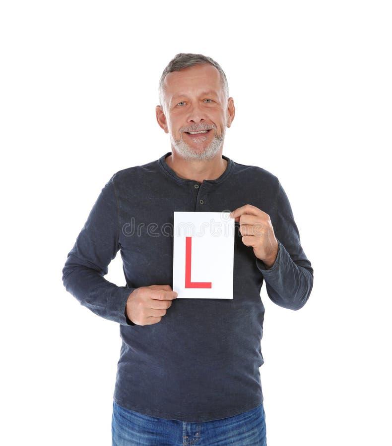 Homme mûr heureux avec le L-plat sur le fond blanc images stock