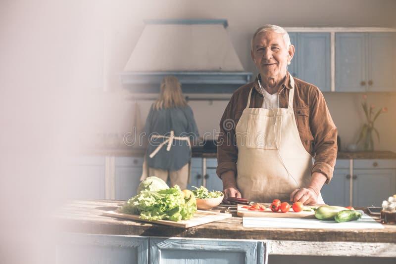 Homme mûr heureux préparant la nourriture saine avec la femme photographie stock libre de droits