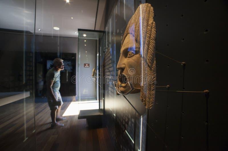 Homme mûr observant le masque de théâtre au centre de visiteurs de Roman Theater de Malaga, Andalousie, Espagne photographie stock libre de droits