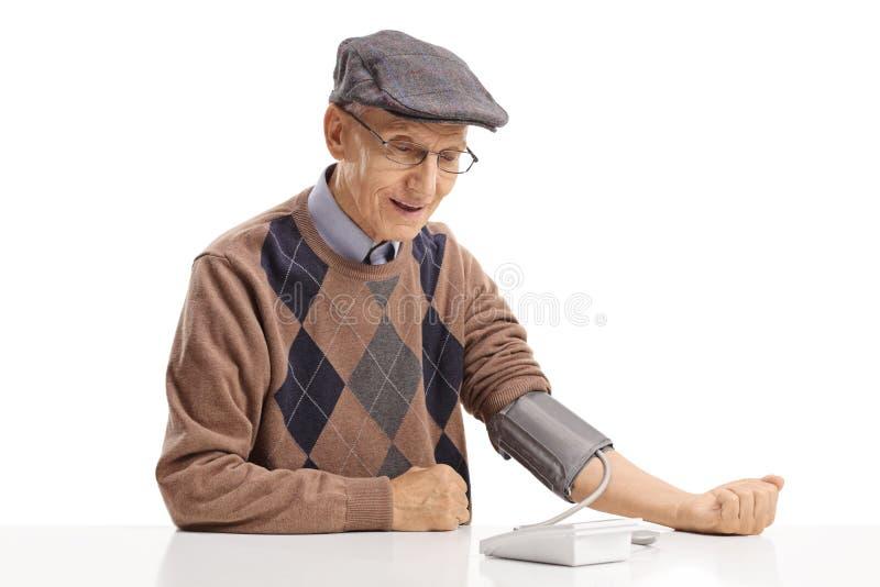 Homme mûr s'asseyant à une table et mesurant sa tension artérielle photos libres de droits