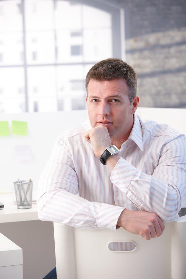 Homme mûr s'asseyant dans penser de bureau images stock