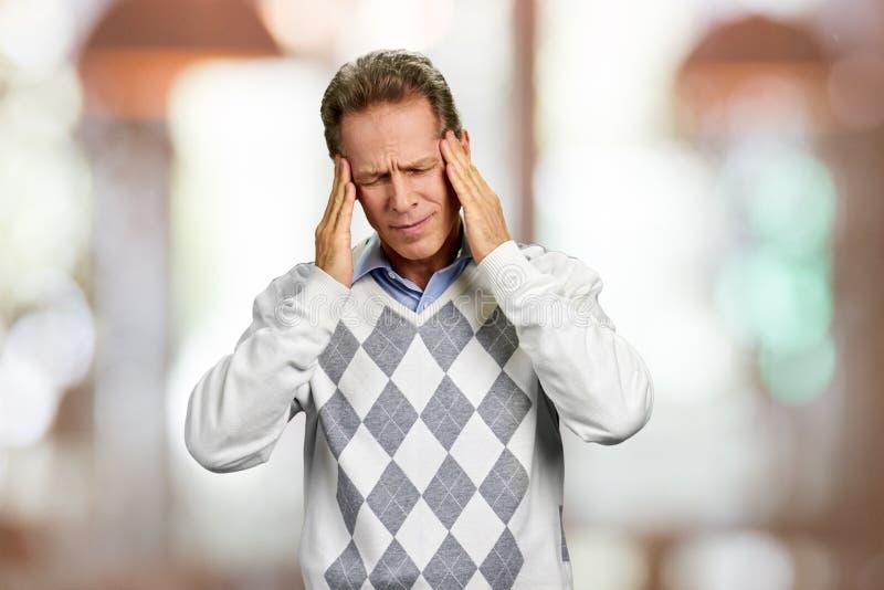 Homme mûr souffrant du mal de tête photos stock