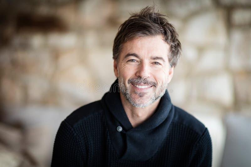 Homme mûr souriant et détendant à la maison photos libres de droits