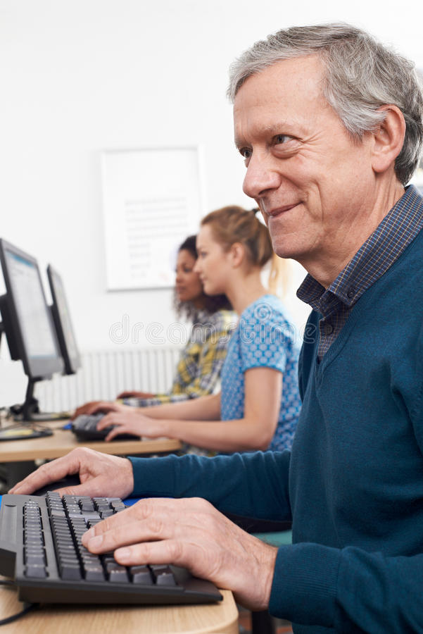 Homme mûr suivant la classe d'ordinateur photos libres de droits