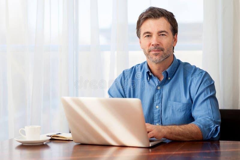 Homme mûr travaillant à la maison dans la cuisine photographie stock libre de droits
