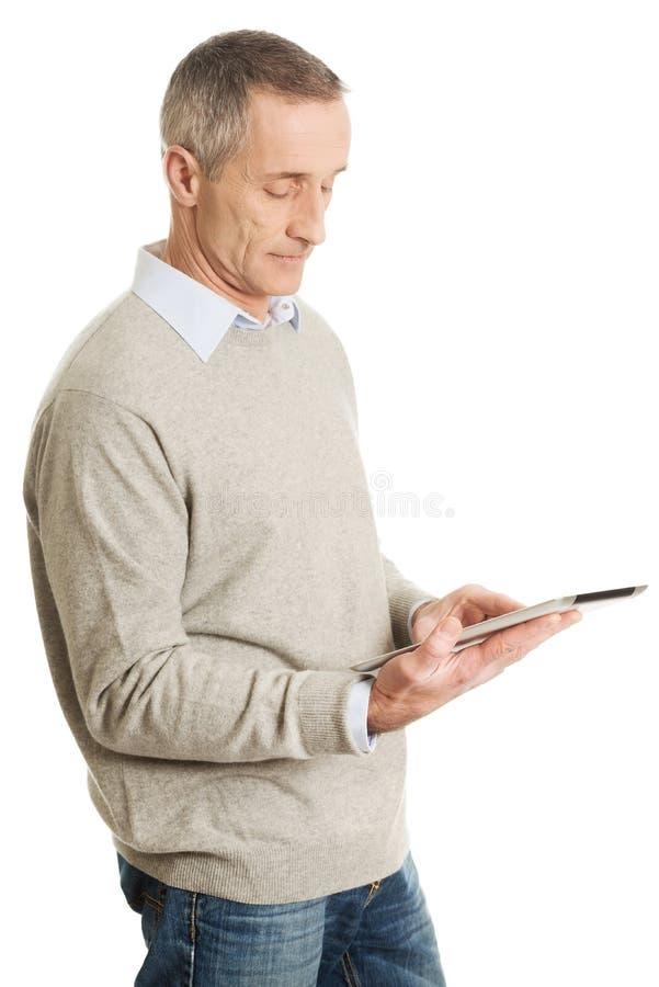 Homme mûr à l'aide de la Tablette de Digital photo stock